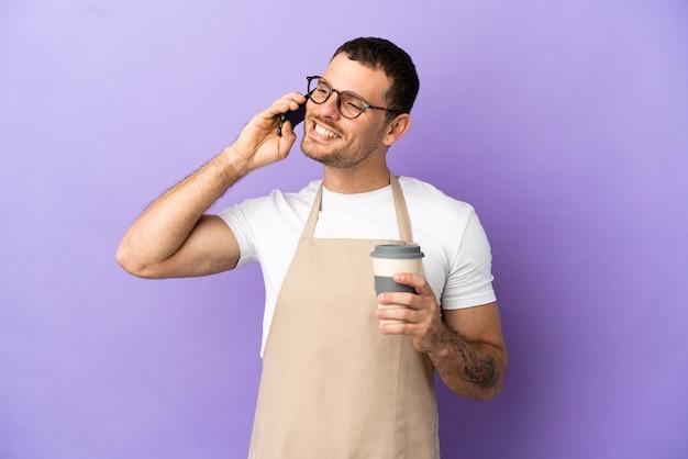 멀리 걸릴 커피와 모바일을 들고 고립 된 보라색 배경 위에 브라질 레스토랑 웨이터