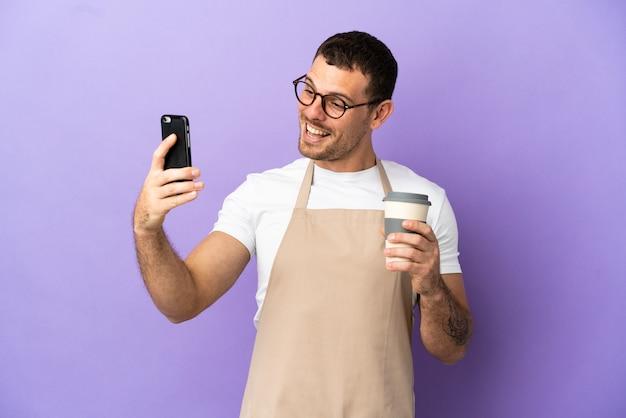 Официант бразильского ресторана на изолированном фиолетовом фоне держит кофе на вынос и мобильный