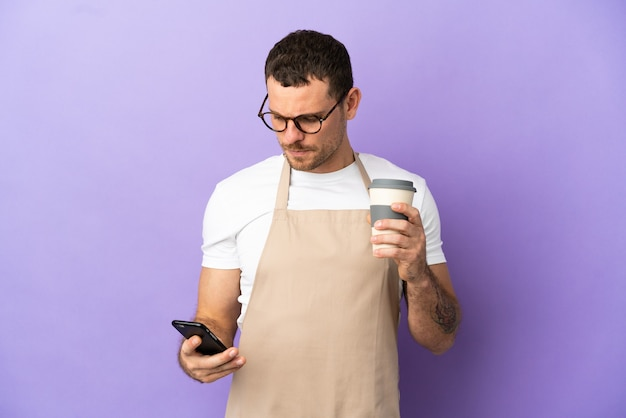 격리된 보라색 배경 위에 있는 브라질 레스토랑 웨이터는 테이크아웃 커피와 모바일을 들고 있습니다.