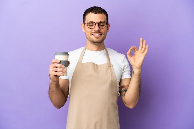 Официант бразильского ресторана на изолированном фиолетовом фоне в позе дзен