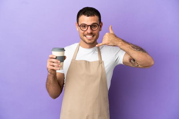 Официант бразильского ресторана на изолированном фиолетовом фоне, делая телефонный жест. перезвони мне знак