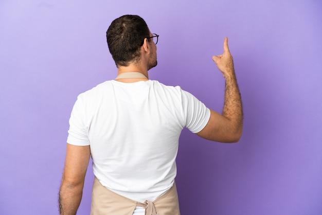 人差し指で後ろ向きの孤立した紫色の背景の上のブラジル料理レストランウェイター