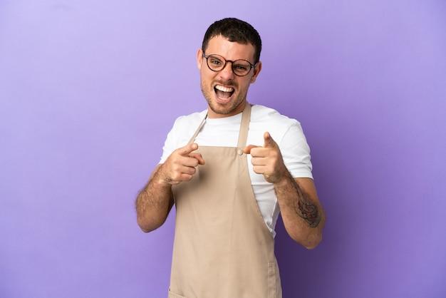 Официант бразильского ресторана на изолированном фиолетовом фоне, указывая вперед и улыбаясь