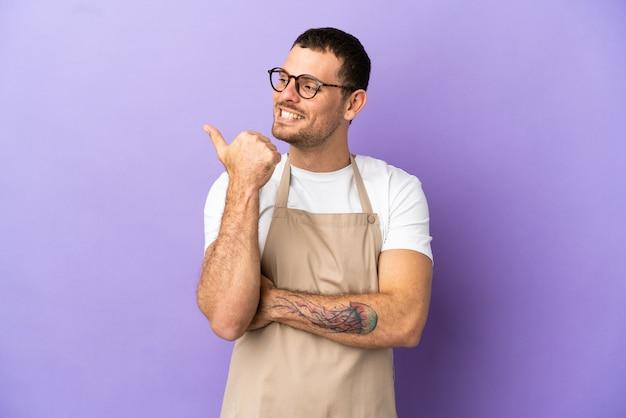Официант бразильского ресторана на изолированном фиолетовом фоне, указывая в сторону, чтобы представить продукт