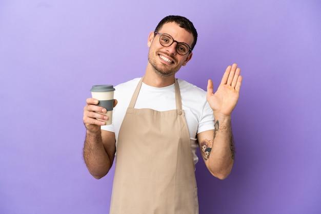 고립된 보라색 배경 위에 행복한 표정으로 손으로 경례하는 브라질 레스토랑 웨이터