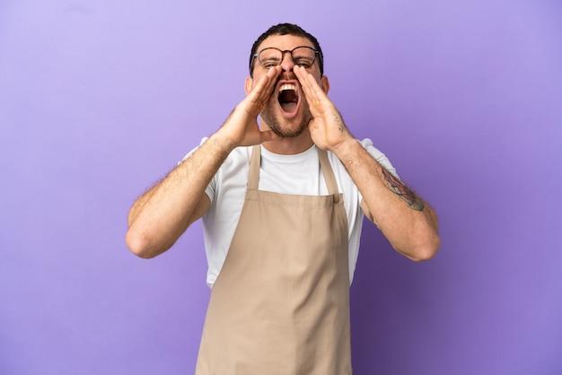 Официант бразильского ресторана на изолированном фиолетовом фоне кричит и что-то объявляет