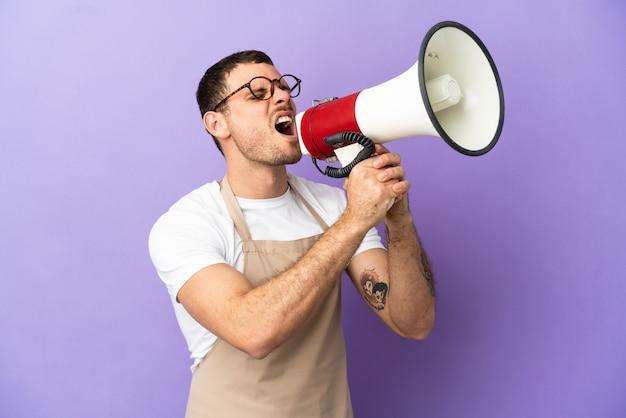 Официант бразильского ресторана на изолированном фиолетовом фоне кричит в мегафон