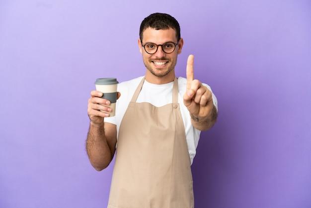 Официант бразильского ресторана на изолированном фиолетовом фоне показывает и поднимает палец