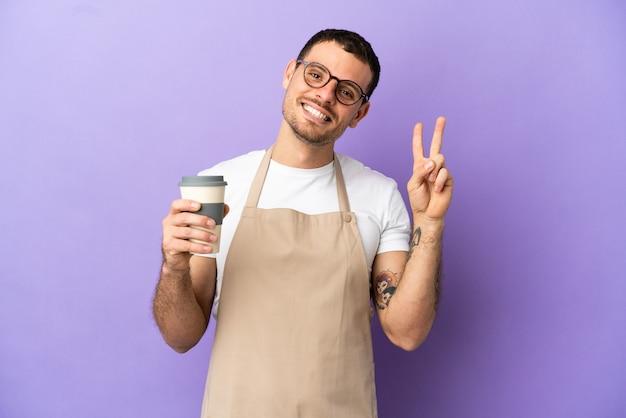 Официант бразильского ресторана на изолированном фиолетовом фоне показывает знак победы обеими руками
