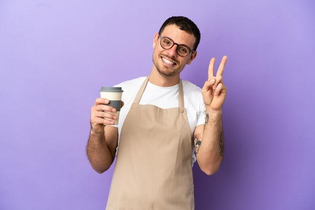 Официант бразильского ресторана на изолированном фиолетовом фоне улыбается и показывает знак победы
