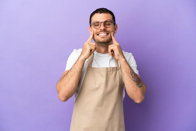 幸せで楽しい表情で笑顔の孤立した紫色の背景の上のブラジル料理レストランウェイター