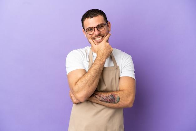 Официант бразильского ресторана на изолированном фиолетовом фоне улыбается