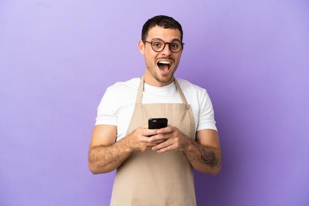 Официант бразильского ресторана на изолированном фиолетовом фоне удивлен и отправляет сообщение