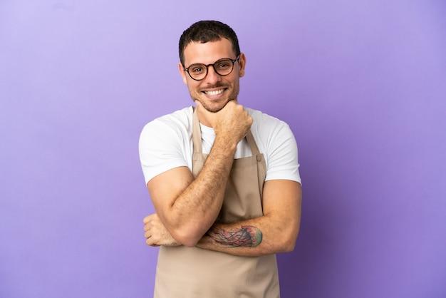 Официант бразильского ресторана на изолированном фиолетовом фоне с очками и улыбкой