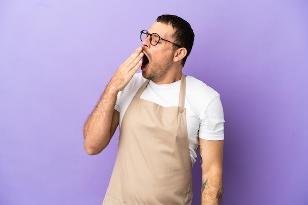 孤立した紫色の背景のあくびと手で大きく開いた口を覆うブラジル料理のレストランのウェイター