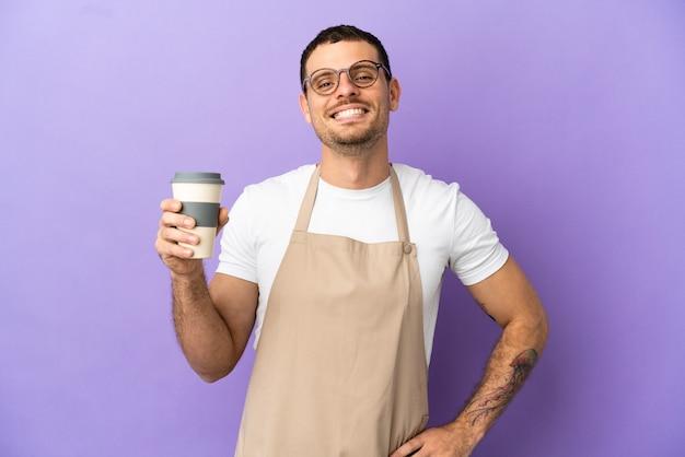 Официант бразильского ресторана над изолированной фиолетовой стеной позирует с руками на бедрах и улыбается