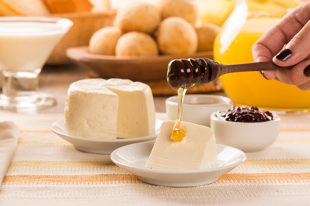 Brazilian sheep cheese. bread, fruits and different types of cheese in the background.