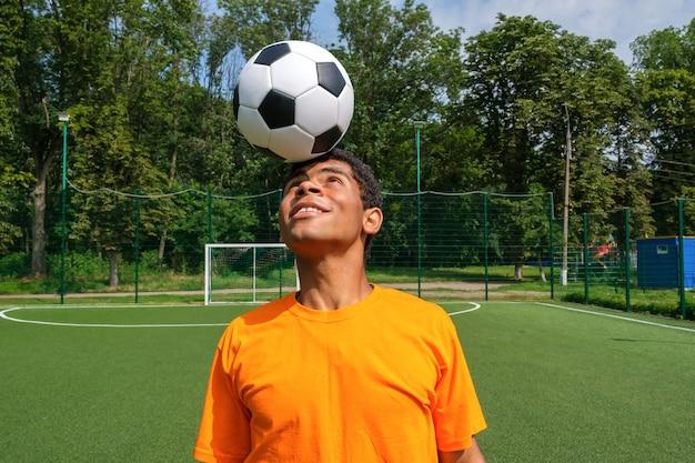 ブラジルのサッカー選手は、スポーツグラウンドでサッカーボールのコントロールをトレーニングおよび改善します