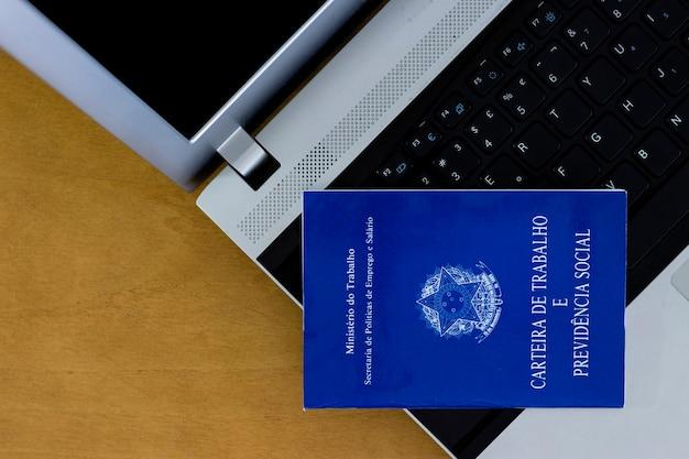 コンピューター上のブラジルの社会保障文書、背景の木製テーブル