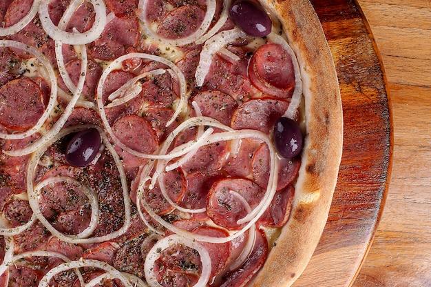 Пицца в бразильском стиле с сыром моцарелла, колбасой пепперони и луком. вид сверху