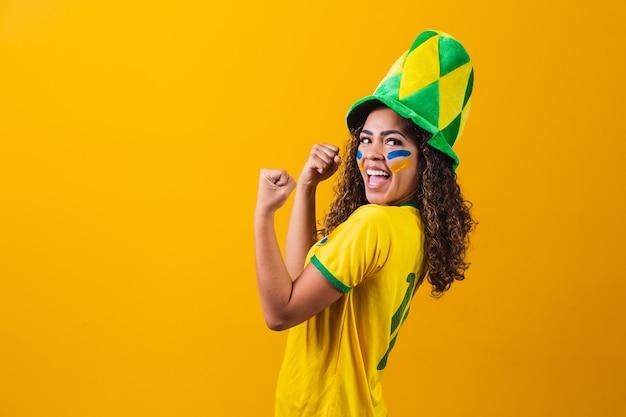 ブラジルのサポーター。黄色の背景でサッカーやサッカーの試合を祝うブラジルの女性ファン。ブラジルの色。はい!