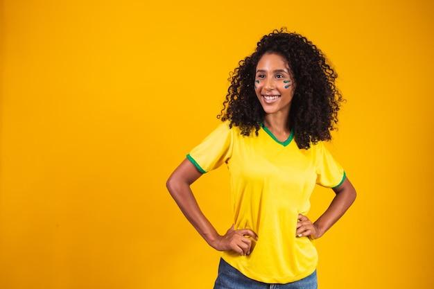 ブラジルのサポーター。黄色の背景でサッカーやサッカーの試合を祝うブラジルの女性ファン。ブラジルの色。