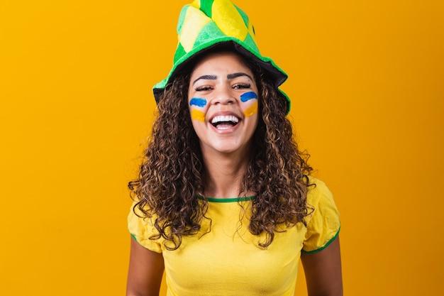 ブラジルのサポーター。コピースペースと黄色の背景でサッカーやサッカーの試合を祝うブラジルの女性ファン。ブラジルの色。