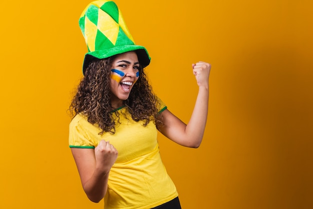 Brazilian supporter. brazilian woman fan celebrating on soccer or football match on yellow background. brazil colors. yes!