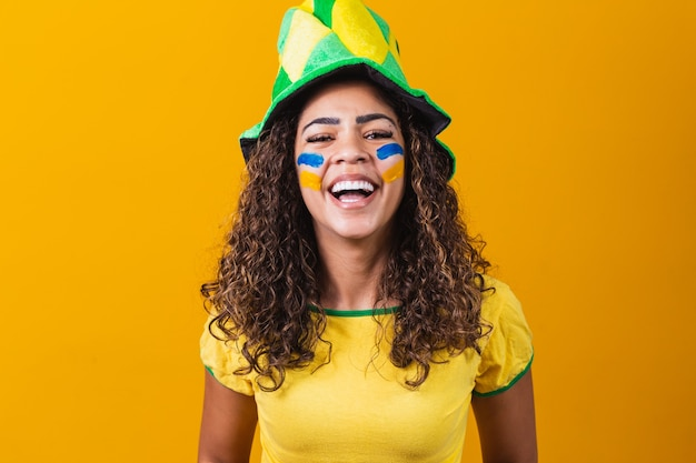 Brazilian supporter. brazilian woman fan celebrating on soccer or football match on yellow background with copy space . brazil colors.