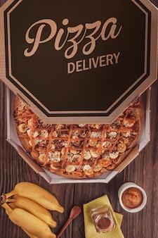 Бразильская сладкая пицца с бананом, дульсе де лече и корицей в коробке доставки - вид сверху.