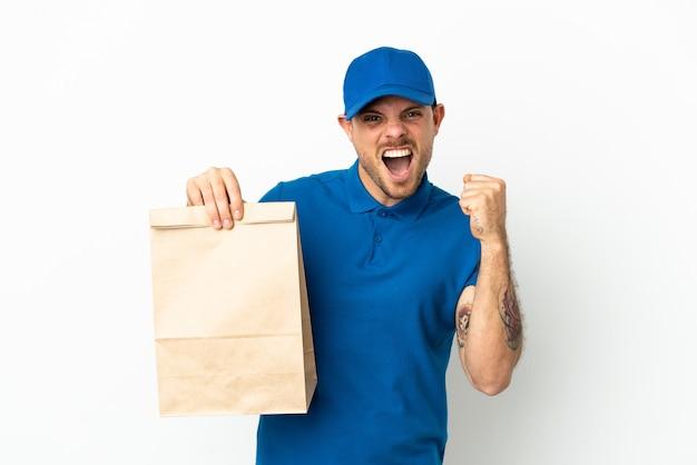 Бразилец берет сумку еды на вынос, изолированную на белом фоне, празднует победу в позиции победителя