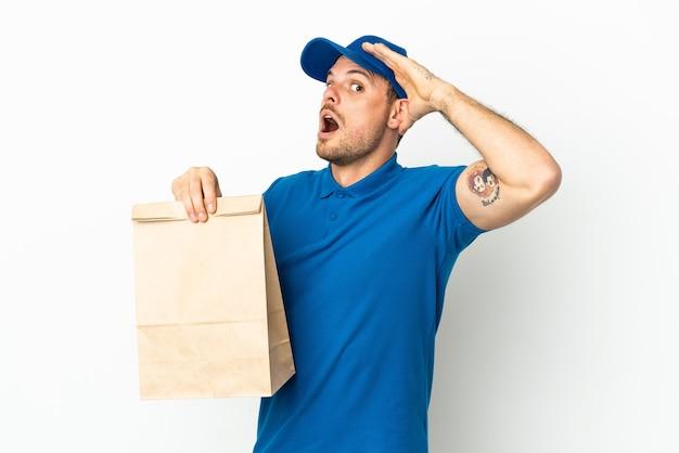 브라질 측면을 보면서 깜짝 제스처를 하 고 흰색 배경에 고립 된 테이크 아웃 음식 가방을 복용