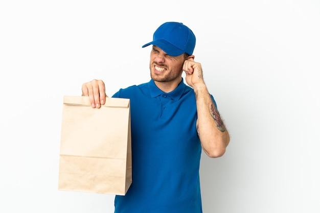 Бразилец берет сумку еды на вынос, изолированную на белом фоне, разочарован и закрывает уши