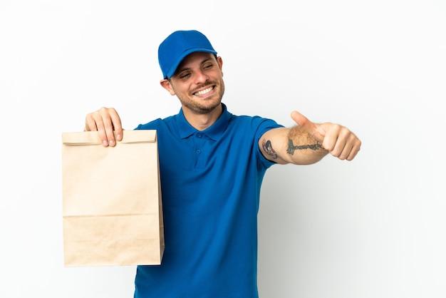 Бразилец берет сумку еды на вынос, изолированную на белом фоне, показывает палец вверх