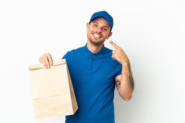 Бразилец берет сумку с едой на вынос, изолированную на белом фоне, показывает палец вверх