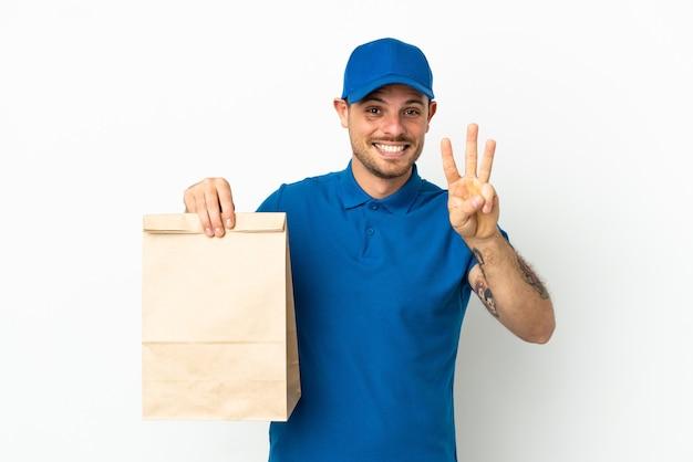 Бразилец берет сумку еды на вынос, изолированную на белом фоне, счастлив и считает три пальцами