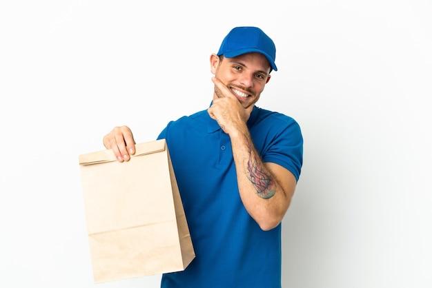 행복하고 웃는 흰색 배경에 고립 된 테이크 아웃 음식 가방을 들고 브라질