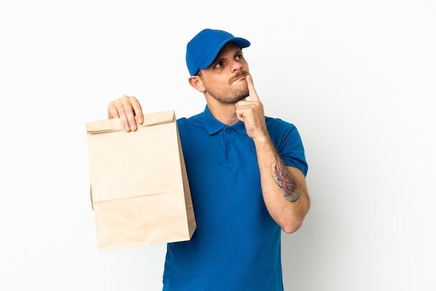 브라질을 찾는 동안 의심을 갖는 흰색 배경에 고립 테이크 아웃 음식 가방을 복용