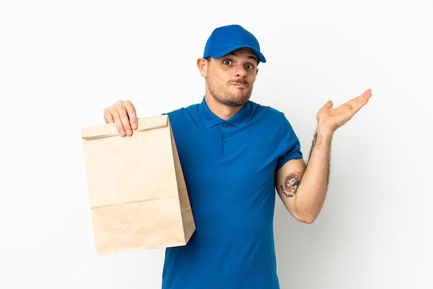 Бразилец берет сумку еды на вынос, изолированную на белом фоне, сомневается, поднимая руки