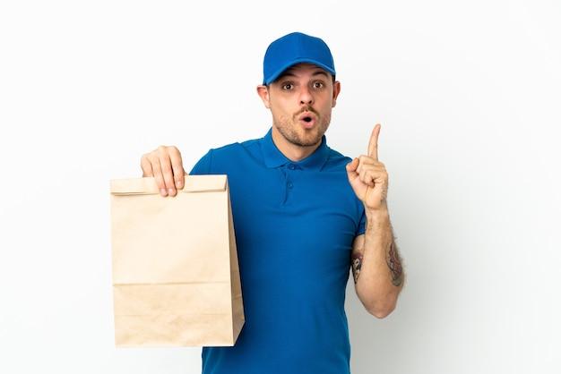 브라질은 손가락을 들어 올리는 동안 솔루션을 실현하려고 흰색 배경에 고립 된 테이크 아웃 음식 가방을 복용