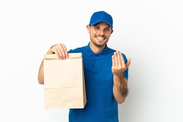 Бразилец, принимая сумку еды на вынос, изолированные на белом фоне, приглашая прийти с рукой. счастлив что ты пришел