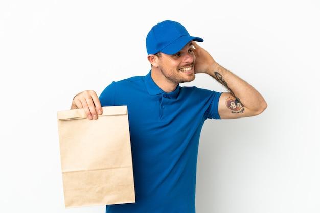 Бразилец берет сумку еды на вынос изолирован на белом фоне, слушая что-то, положив руку на ухо