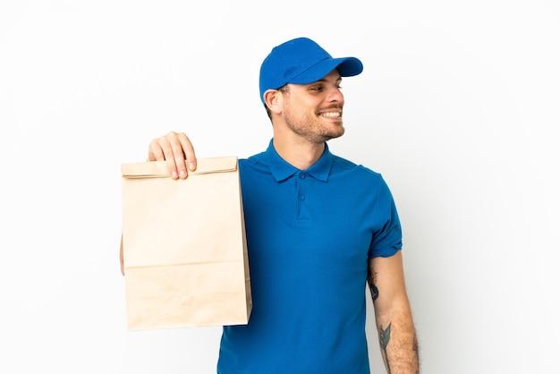 Бразилец берет сумку еды на вынос, изолированную на белом фоне, смотрящую сторону