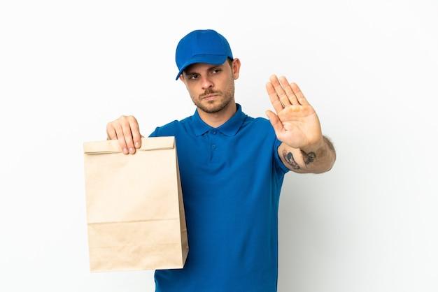 Бразилец берет сумку еды на вынос, изолированную на белом фоне, делая жест стоп и разочарованный