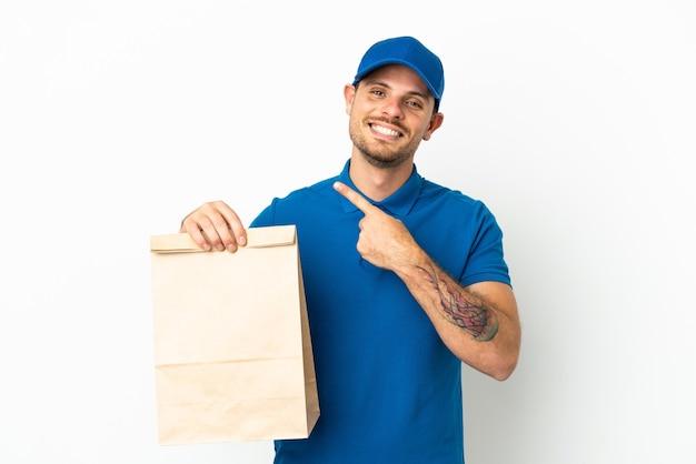 Бразилец берет сумку еды на вынос, изолированную на белом фоне, указывая в сторону, чтобы представить продукт