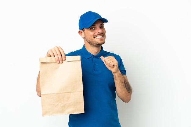Бразилец берет сумку еды на вынос, изолированную на белом фоне, гордый и самодовольный