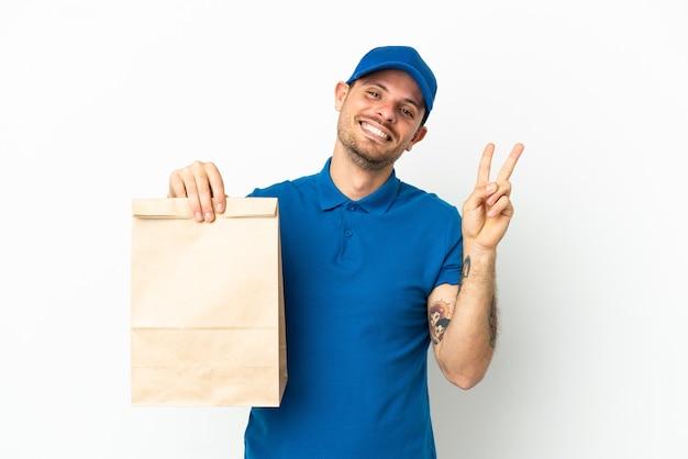 Бразилец берет сумку еды на вынос, изолированную на белом фоне, улыбается и показывает знак победы
