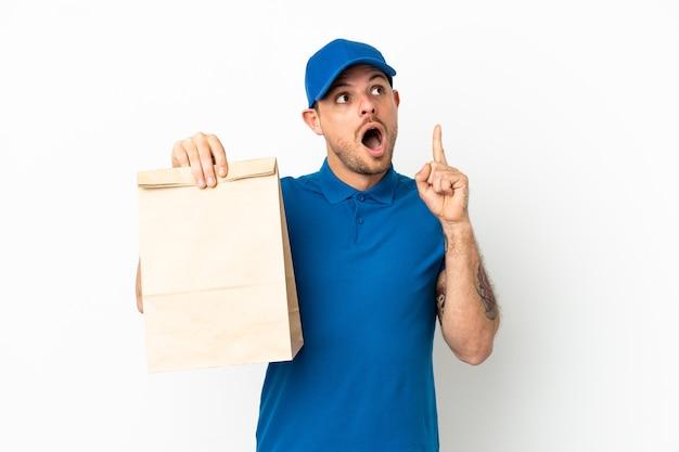 Бразилец берет сумку еды на вынос изолирован на белом фоне, думая об идее, указывая пальцем вверх