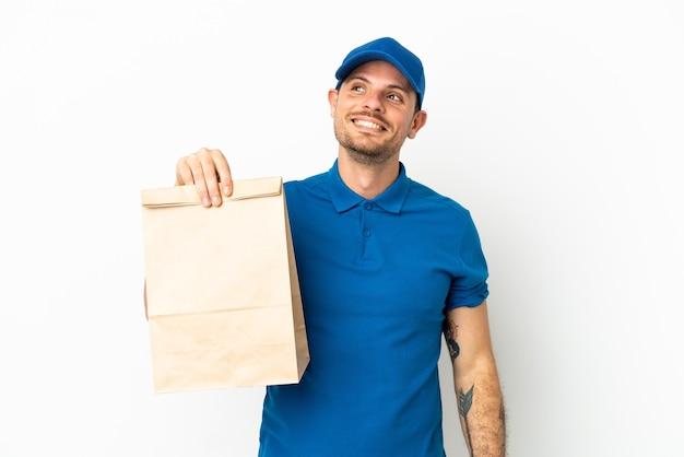Бразилец берет сумку еды на вынос, изолированную на белом фоне, думая об идее, глядя вверх