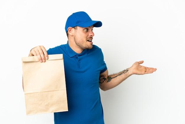 Бразилец берет сумку еды на вынос, изолированную на белом фоне с удивленным выражением лица, глядя в сторону